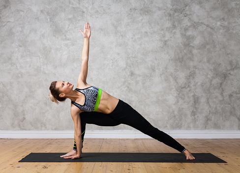 young woman practicing yoga pose bikram triangle