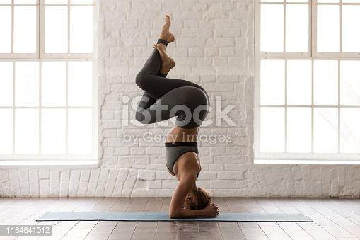 Young beautiful woman practicing yoga, standing in headstand pose, Garuda salamba sirsasana exercise, sporty girl in grey sportswear, leggings and bra working out at home or in yoga studio side view