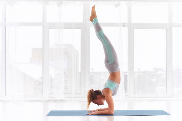 Young woman practicing yoga, standing in Pincha Mayurasana - Forearm stand at the yoga studio stock photo