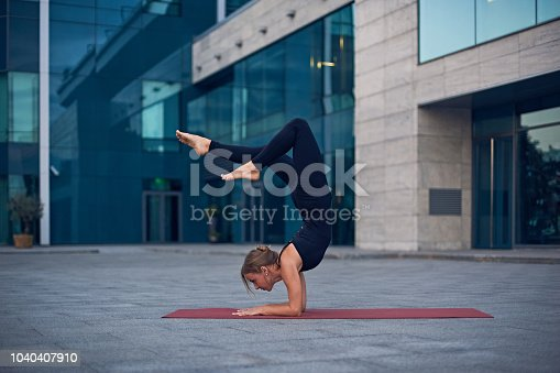 Young woman practicing yoga, standing in Vrischikasana Scorpion pose outdoors against the background of a modern city.