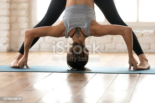 Young sporty attractive woman practicing yoga, doing Wide Legged Forward Bend exercise, Prasarita Padottanasana pose, working out, wearing sportswear, pants and top, indoor close up, white yoga studio