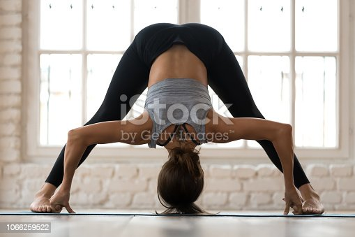 Young sporty attractive woman practicing yoga, doing Wide Legged Forward Bend exercise, Prasarita Padottanasana pose, working out, wearing sportswear, pants and top, indoor full length, yoga studio