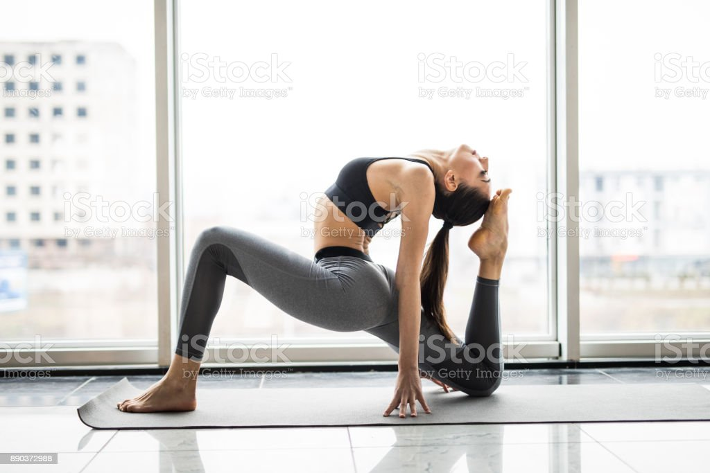 Young woman practicing yoga with panoramic windows in the background. Freedom concept. Calmness and relax, woman happiness. stock photo