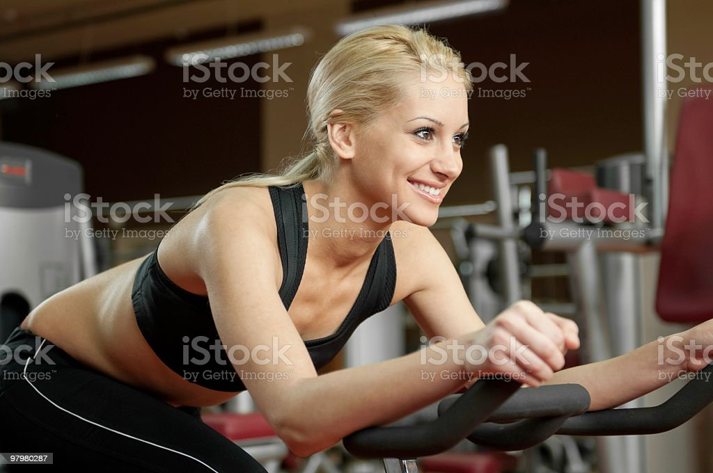 Young woman practicinng with speedbike in the gym royalty-free stock photo