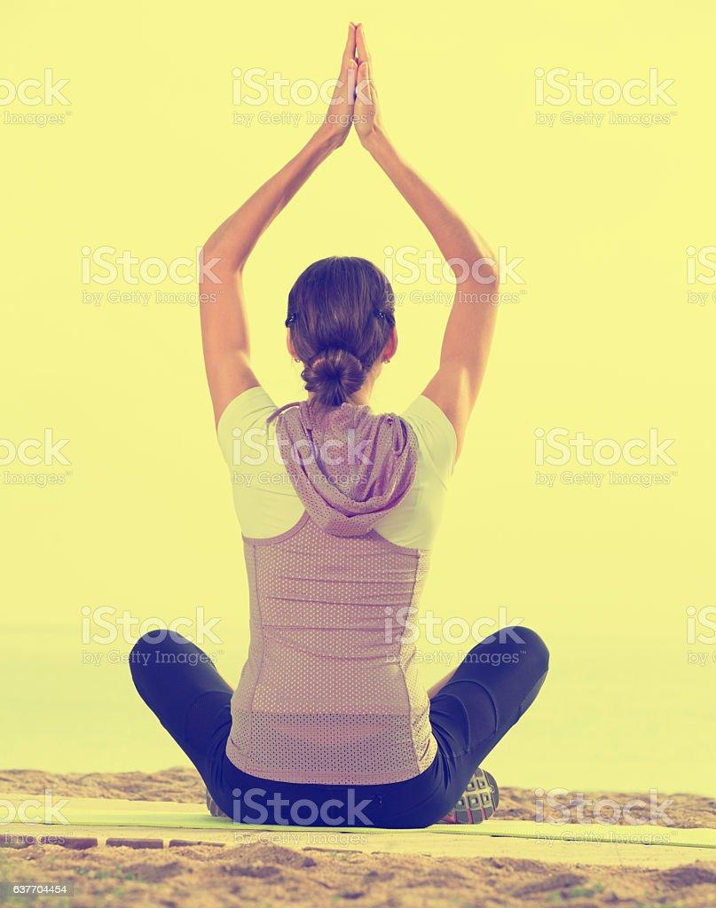 Young woman practise yoga cross-legged stock photo