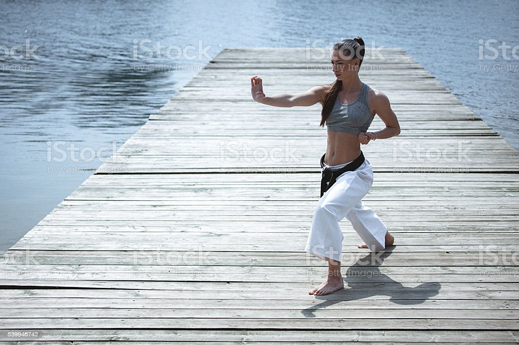 Young woman practising karate outdoors stock photo