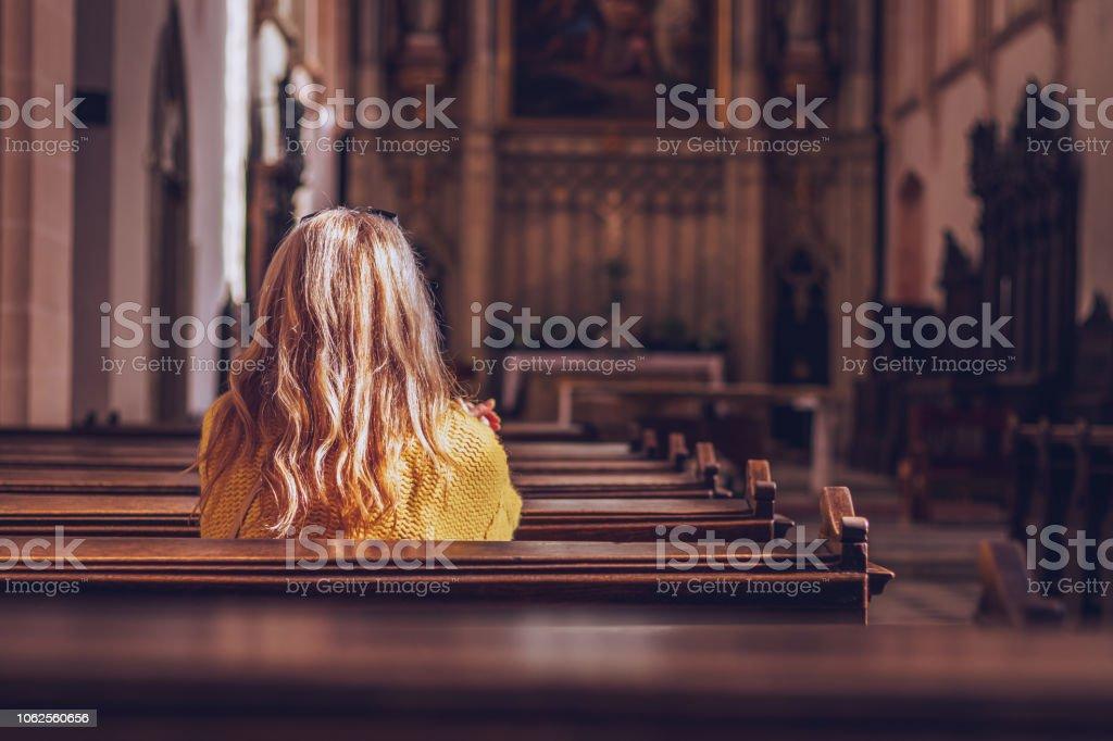 年輕女子在教堂裡祈禱和冥想。天主教大教堂與宗教的標誌 - 免版稅一個人圖庫照片