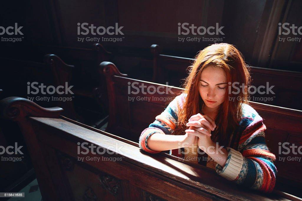 Young woman praying in church stock photo