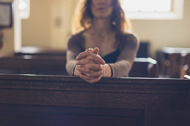 Young woman praying in church A young woman is sitting with her hands folded and is praying in a church pew stock pictures, royalty-free photos & images