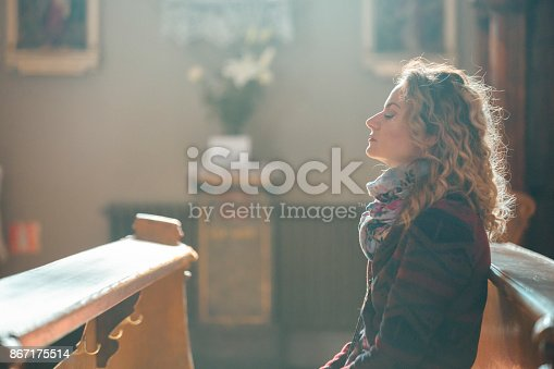 Young woman praying in the church.
