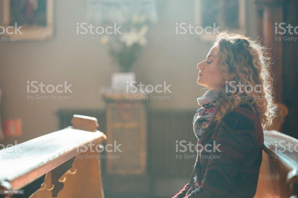 Jeune femme priant dans l'église. - Photo