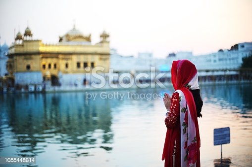 Young woman of Indian ethnicity wearing red color traditional cloths she standing in Golden Temple and praying to God in Amritsar, Punjab India. The Golden Temple, also known as Sri Harmandir Sahib (