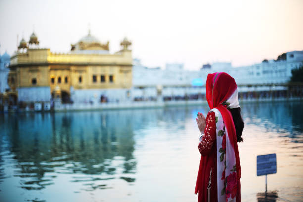 Young woman praying to God in Golden Temple, India Young woman of Indian ethnicity wearing red color traditional cloths she standing in Golden Temple and praying to God in Amritsar, Punjab India. The Golden Temple, also known as Sri Harmandir Sahib (