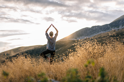 Young woman preforms yoga in mountains in morning light