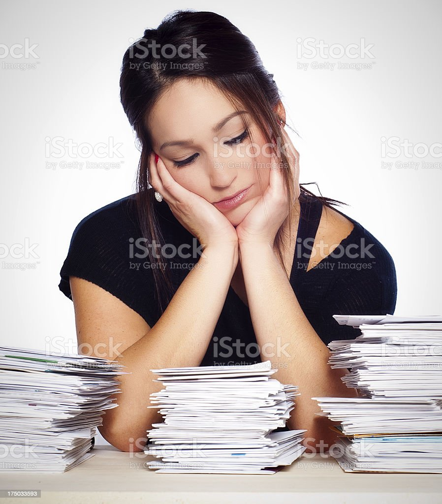 Young Woman Preoccupied with Unpaid Bills and Paperwork Overload royalty-free stock photo