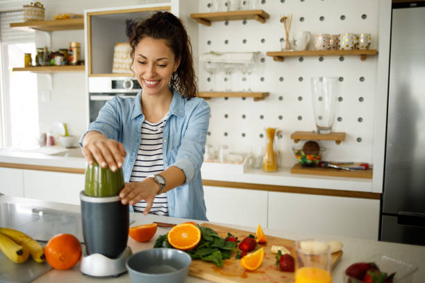 Young woman preparing a green smoothie at home stock photo