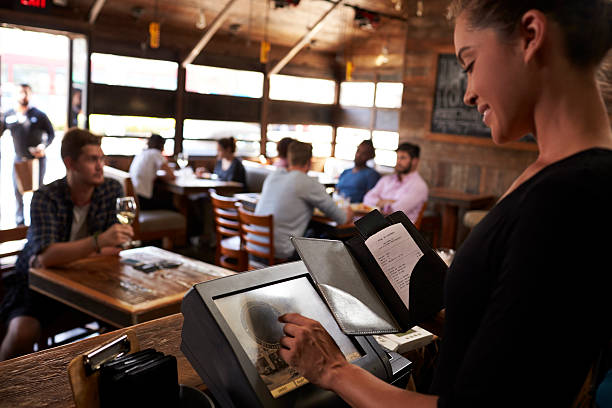 Young woman preparing bill at restaurant using touch screen stock photo