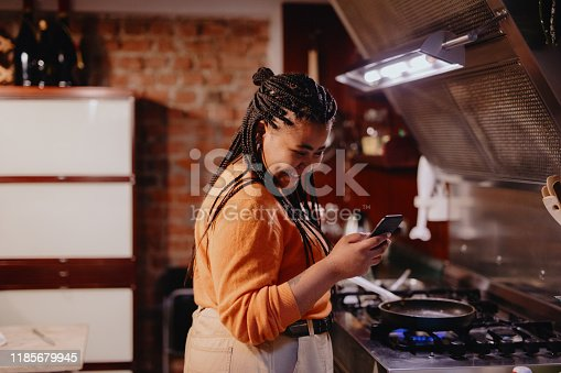 Young woman preparing breakfast and smiling while looking at her phone