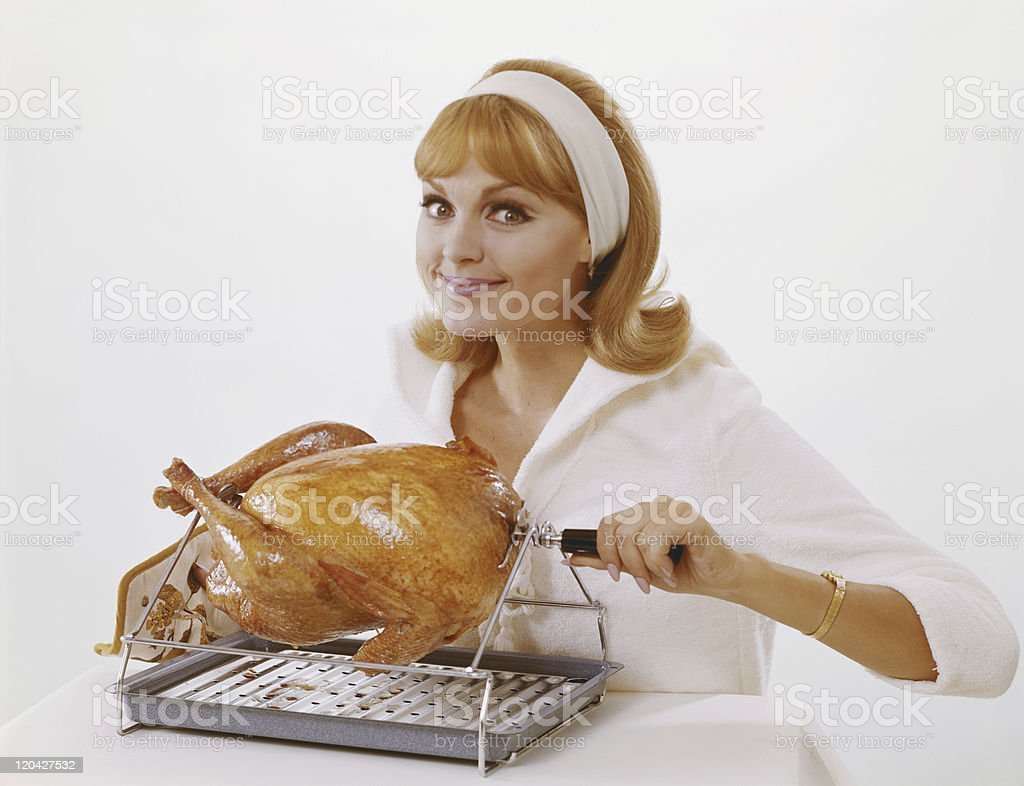 Young woman preparing chicken on spit roast against white background, portrait royalty-free stock photo