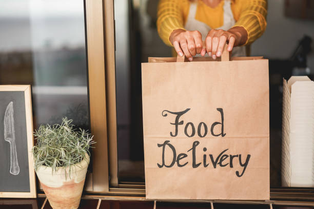 Young woman preparing food delivery inside ghost kitchen during quarantine isolation time - Take away meal for online order - Sustainable and healthy food concept - Focus on hands stock photo