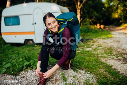 Young female hiker tying a shoelace and preparing for a hiking tour.