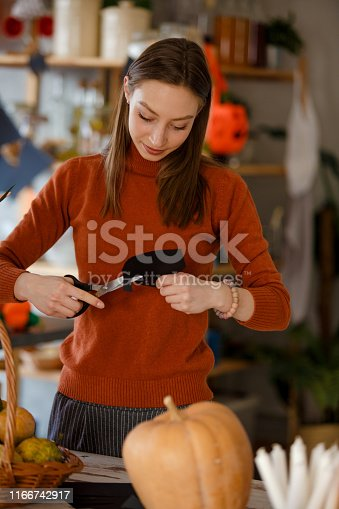 Young woman making paper Halloween decorations.