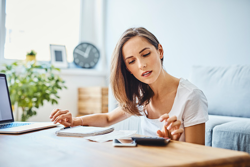 istock Young woman preparing home budget, using laptop and calculator 1151155735