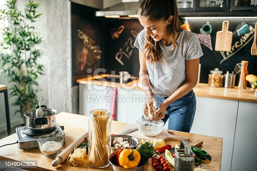 Photo of young woman preparing pizza at home