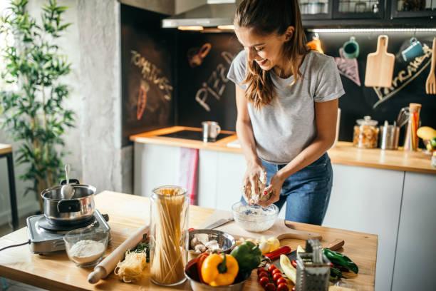 giovane donna che prepara la pizza - cucinare foto e immagini stock
