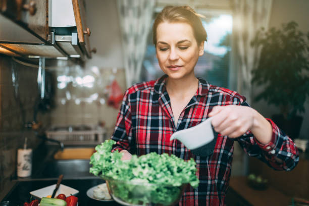 Young woman preparing salad in the kitchen stock photo