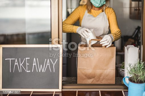 Young woman preparing takeaway healthy food inside restaurant during Coronavirus outbreak time - Worker inside kitchen cooking vegetarian food for online order service - Focus on salad