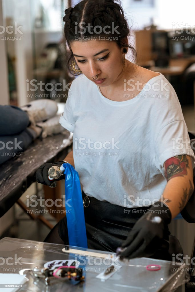 Young woman preparing the tattoo machine and inks. стоковое фото