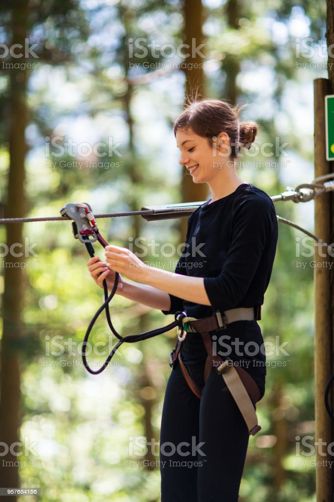Young woman preparing to go on a zip line through the forest stock photo