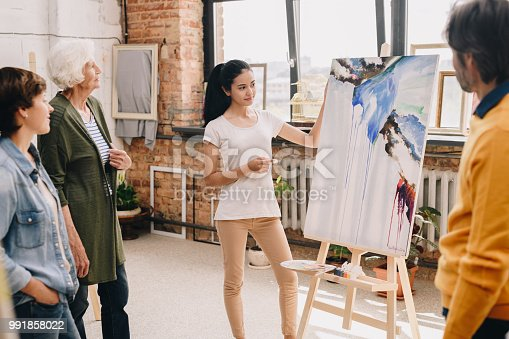 Portrait of pretty young woman presenting modern watercolor painting to audience standing in art-studio or gallery