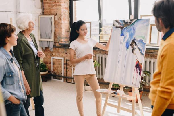 그림을 제시 하는 젊은 여자 - 예술 뉴스 사진 이미지