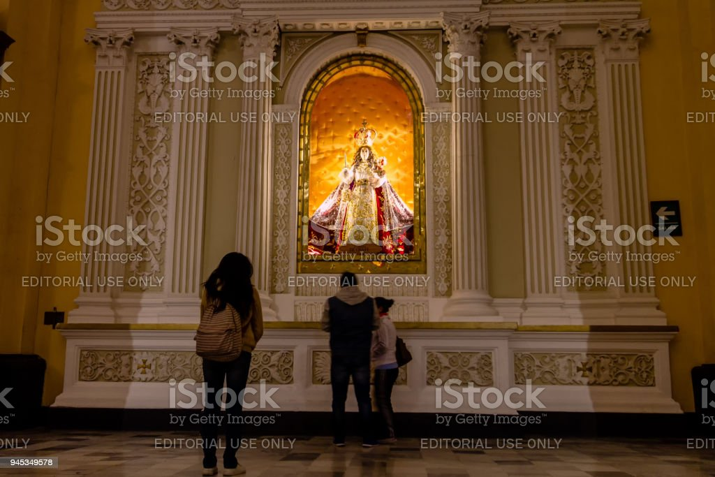 A young woman presents her respects in front of the image of the Virgin of Chapi while other faithful pass by in the central chapel of the Cathedral of Arequipa stock photo