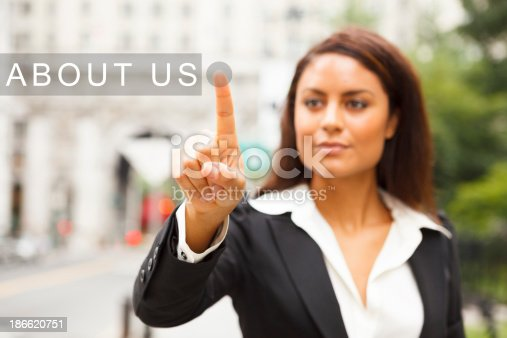 A young well dressed woman on a city street presses a virtual ABOUT US button suspended in mid-air.