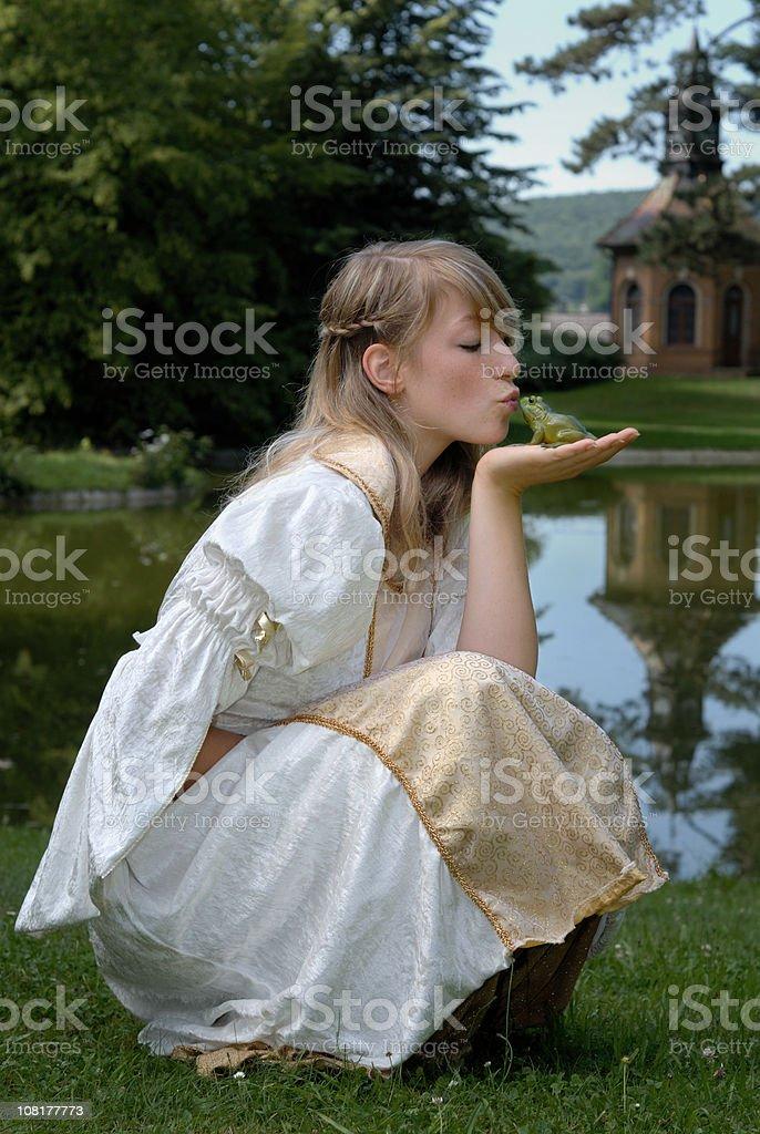 Young Woman Princess Kissing Frog Near Pond stock photo