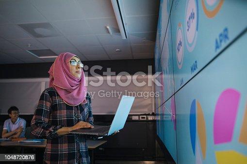 istock Young Woman Programming a Data Presentation 1048720876
