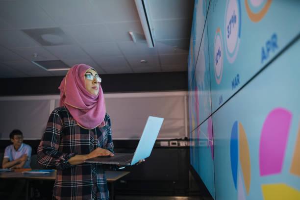 young woman programming a data presentation - скромная одежда стоковые фото и изображения