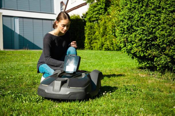 Young Woman Programming Robotic Lawn Mower stock photo