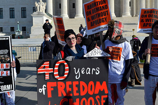 Young Woman Protesting At U.S. Sumpreme Court Washington D.C., USA - January 22, 2015; A Young woman holds a pro-choice sign at the U.S. Supreme Court in Washington D.C. pro choice stock pictures, royalty-free photos & images