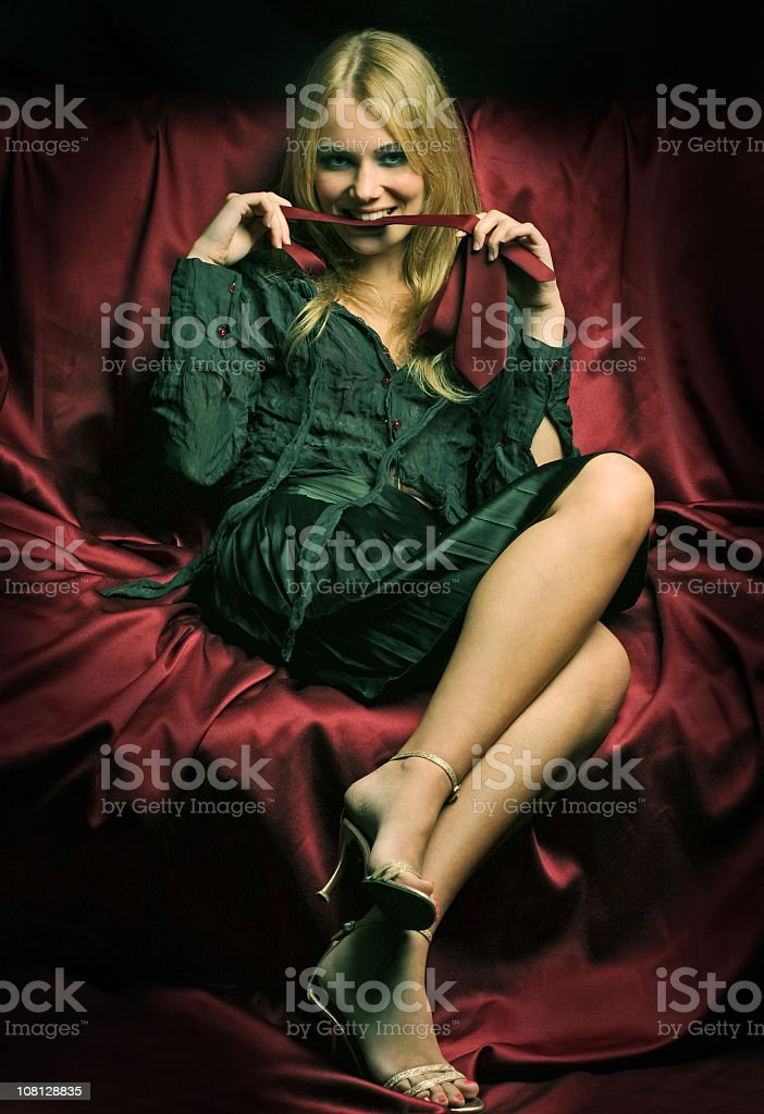 Young Woman Provocatively Biting Tie Stock Photo