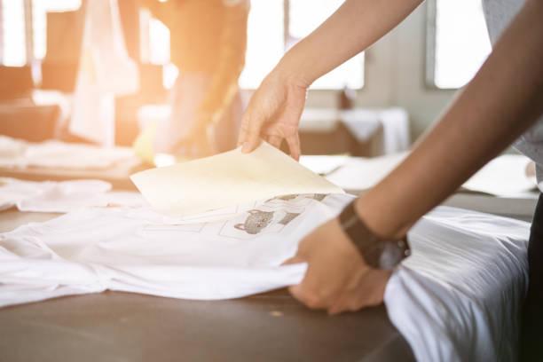 Jovem mulher puxe o papel da película impermeável sobre o tecido na loja. trabalhador manual de serigrafia na camiseta a trabalhar. - foto de acervo