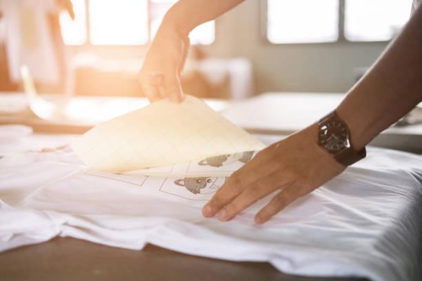 Junge Frau herausziehen Papier aus wasserdichten Folie auf Stoff im Shop. Arbeitnehmer arbeitet an manuellen Siebdruck auf T-shirt. – Foto