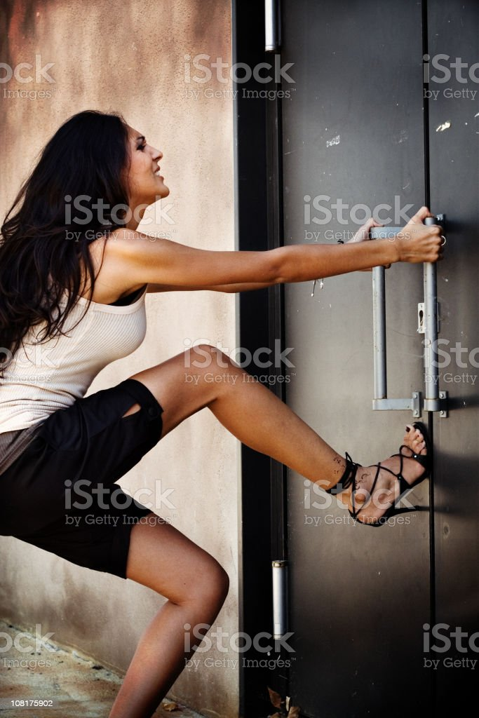 Young Woman Pulling on Door stock photo