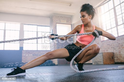 istock Young woman pulling rope at gym. 638029262