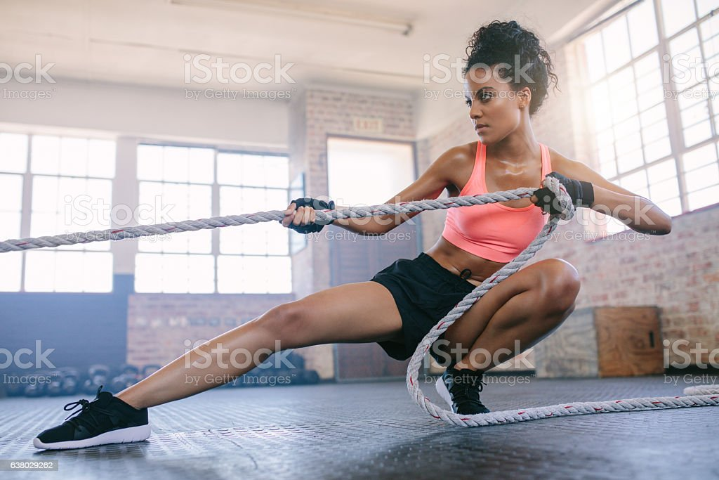 Young woman pulling rope at gym. stock photo
