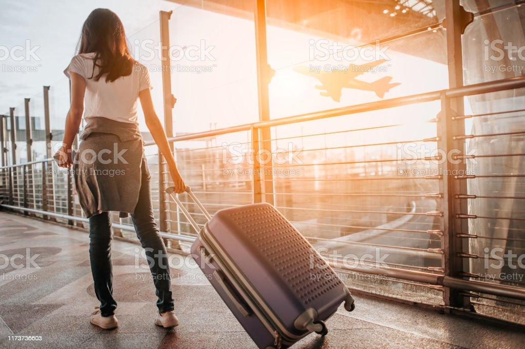 Havaalanı terminalinde bavulu çeken genç kadın. Kopyalama alanı - Royalty-free 13 - 19 Yaş arası Stok görsel