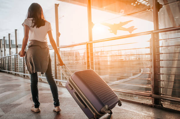 Young woman pulling suitcase in  airport terminal. Copy space Young woman pulling suitcase in  airport terminal. Copy space travel stock pictures, royalty-free photos & images